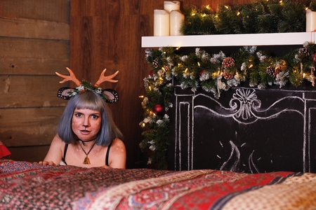 Beautiful girl in a Christmas deer costume on bed