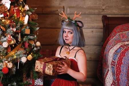 Beautiful girl in a Christmas deer costume near to Christmas tree and new year presents Фото со стока
