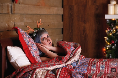 Beautiful girl in a Christmas deer costume lie in bed