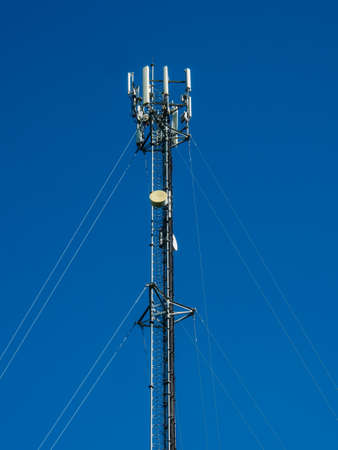 communicable: The phone antenna on blue sky. Stock Photo