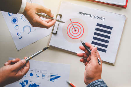 Business team together pointing to business goals, business goal concept