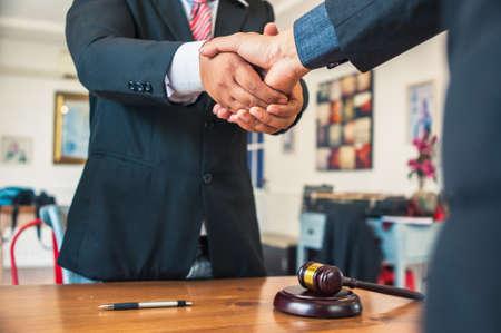 Advocaten en zakenlieden slaan de handen ineen na ondertekening van het juridisch adviescontract