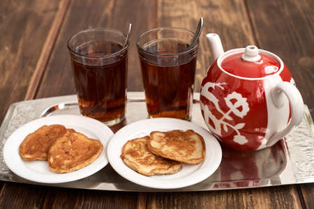 old styled: glassful teapot tea pancakes in Russian style Stock Photo