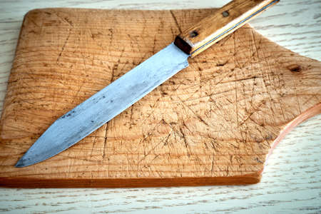 An old rugged cutting board and a spent knife Banque d'images