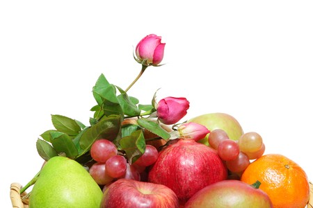 Rose buds and basket of colorful fruits isolated on white photo