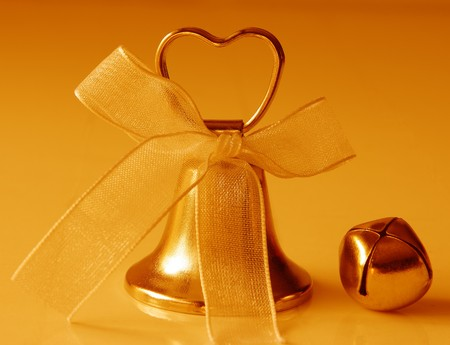 Two tiny gold jingle bells with bow agains warming background Stock Photo - 4248975