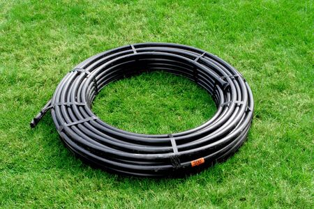 Coil of black poly pipe on green grass yard, springkler system part