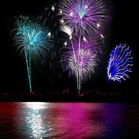 Blue purple white and cyan fireworks reflecting on the lake Reklamní fotografie