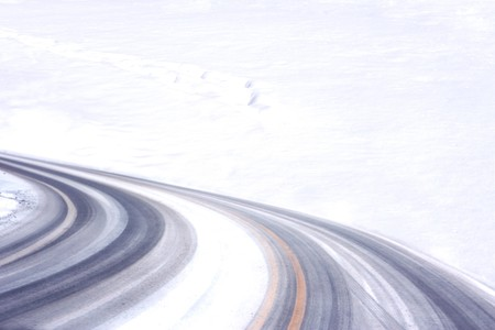 sidelit: Tire tracks on the road by the snow field