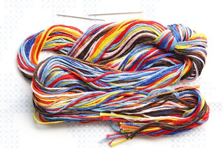 Bundle of colorful embroidery threads on stamped cross stitch photo