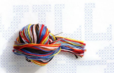 darn: Multi color embroidery thread ball with needles on stamped cross stitch