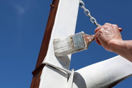 cartilla: El hombre de la mano de pintura a un primer polo de metal oxidado