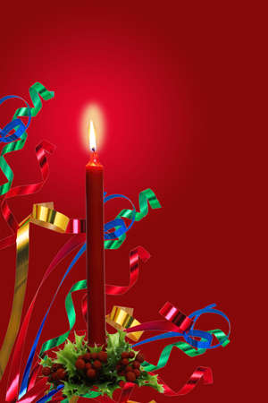 liturgy: Flaming candle and ribbons on sprig of holly base over red background Stock Photo