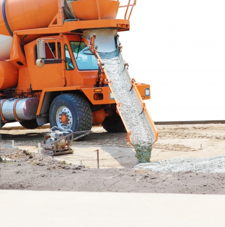 Concrete mixer truck pouring cement down to the drive way photo