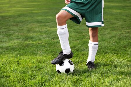 soccer cleats: Close up of a boys legs wearing cleets and ball Stock Photo