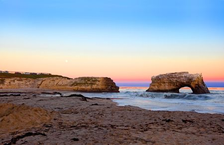 erosion: Sea arch formed by wave erosion at Natural Bridges State park at the sunset