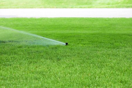 Sprinkler system watering the lawn in the summer photo