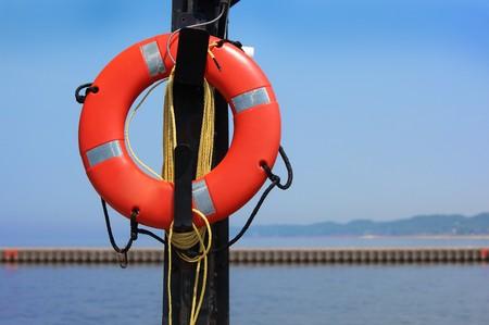 salvavidas: Anillo de salvamento de espuma de Bouyant por la orilla del lago Foto de archivo