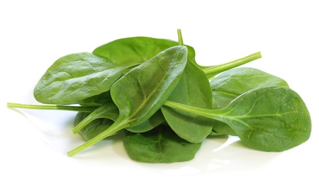 Pile of fresh baby spinach leaves over white