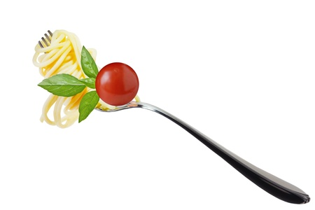 Spaghetti on the fork with cherry tomato and basil