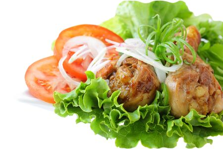Fried chicken thighs with green lettuce, tomatoes, and onion Banque d'images