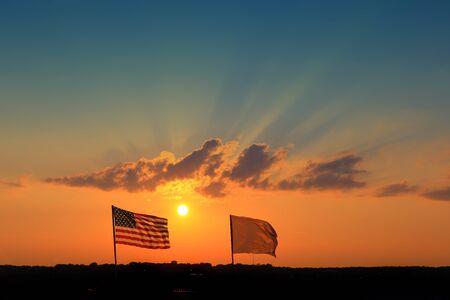前の空港で夕日を背景にアメリカの国旗