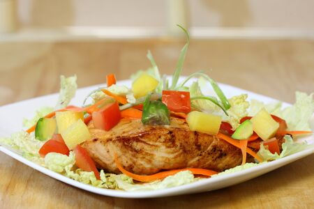 Grilled salmon with napa cabbage, carrot, tomato, and pineapple photo