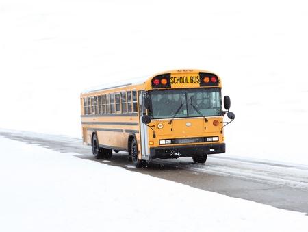農村道路上で冬の運転の学校のバス