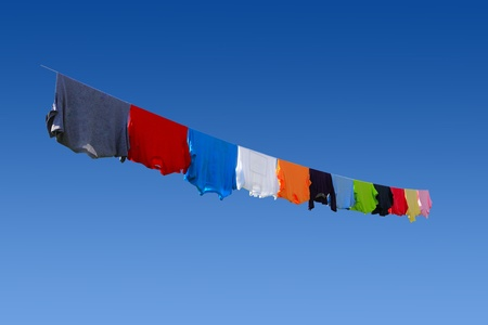 Colorful T-shirts hanging on clothesline in summer time photo