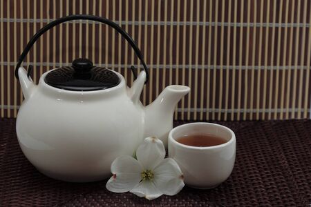 tetsubin: Teapot and cup of tea over bamboo background Stock Photo