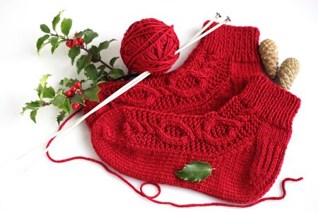 Red knitting homemade socks with holly branch Фото со стока