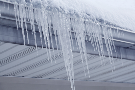 eaves: Icicles hanging on gutter eaves of roof in winter time