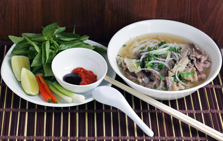 Pho Beef noodle soup eating with basil