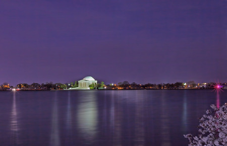Thomas Jefferson Memorial illuminated at night with the tidal basin in the foreground during the peak cherry blossom festival