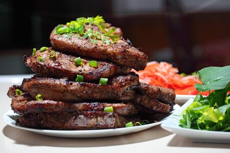 Delicious juicy grilled pork chop steak with fresh homegrown vegetable salad, tomatoes, sweet and sour carrot, radish. Hot Meat Dishes.