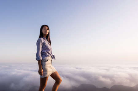Portrait of a woman on top of a mountain above the clouds during sunset