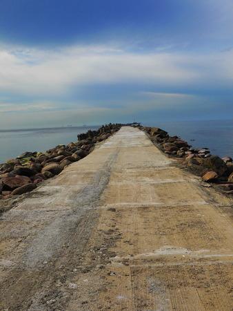 going in: Ruinas de la carretera de piedra que van en el mar Foto de archivo
