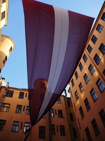 Huge Latvian Flag between old buildings in Old town photo