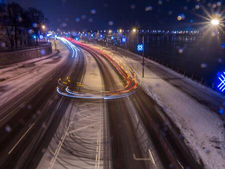 Car light in night on ice road in snow winter, Latvia photo