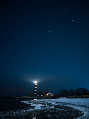 Riga Lighthouse in a starry night with frozen Baltic sea photo