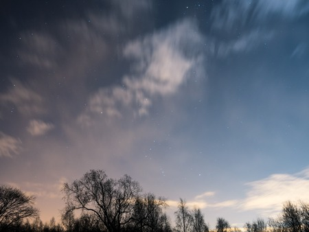 Cloudy sky with moon and stars at night photo