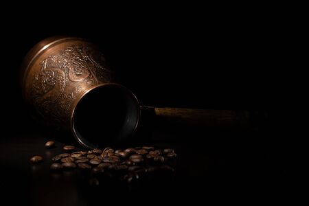 An inverted Eastern Turk with a dragon engraving and scattered coffee beans on a dark background.