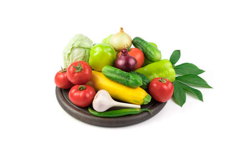 Lots of fresh vegetables on a white background on a wooden Board with a green branch with leaves. Side view. The concept of natural products, proper nutrition. 写真素材