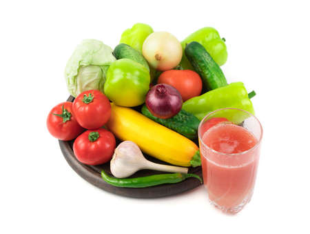 A glass of fresh vegetable juice and a Large selection of fresh vegetables on a round tray on a white background. Plant background. The concept of proper nutrition.