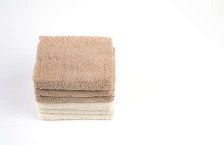Terry towels are white and light brown on a white background. The view from the top view. The concept of home textiles.