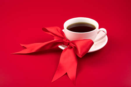 Beautiful composition with a white Cup and a red satin bow on a red background. Romantic background. The concept of the cards, a meeting of lovers.