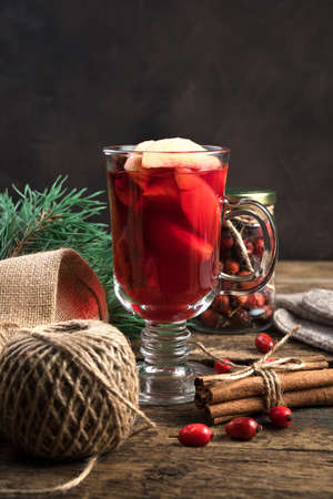 Happy New year and merry Christmas, a warm festive drink with fruit, berries and cinnamon on a wooden background. Concept of holiday backgrounds.