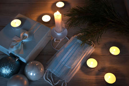 Candles burning in the semi-darkness with protective masks on a wooden background. The concept of Christmas during the coronavirus.