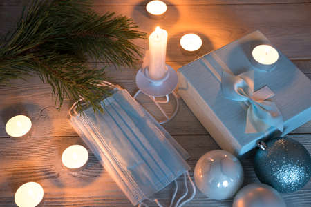 Christmas background with medical masks and burning candles on a wooden background. The concept of a safe Christmas celebration.