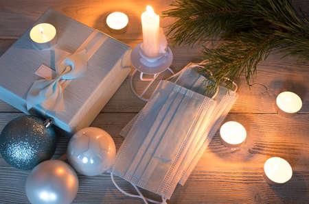 Medical masks among burning candles, gift boxes and Christmas balls. The concept of a safe Christmas celebration.